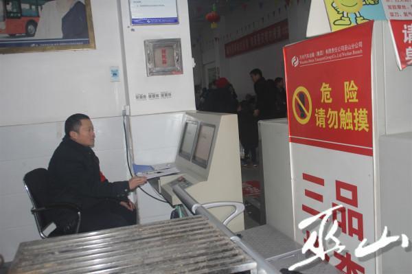 孙国通过安检系统检查旅客的行李。.JPG